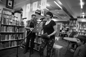 Hinemoana Baker Rachel O'Neill reading a short welcome from Hue & Cry Press publisher Chloe Lane who is currently based in Florida. (Image by Matt Bialostocki)
